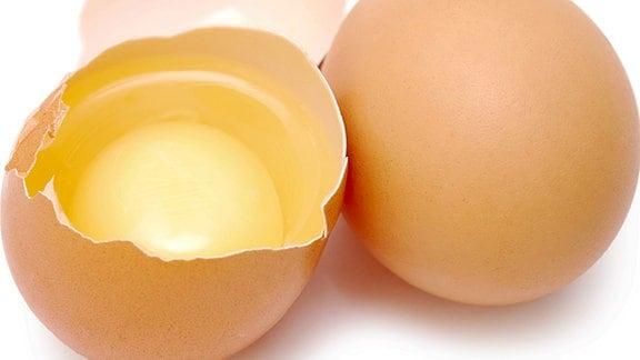 Zwei Eier, nebeneianderliegend. Eines ist aufgeschlagen.