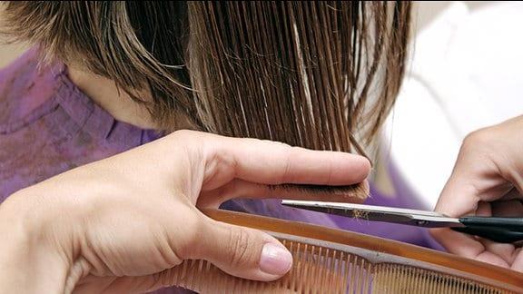 Ein Friseur schneidet einer Person die Haare.