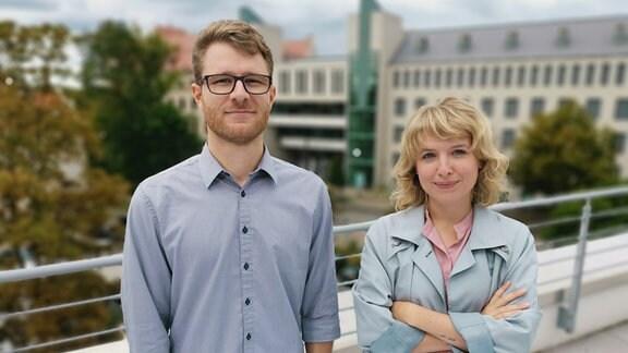 Die beiden MDR-Reporter Roland Jäger und Marie Landes stehen auf einer Dachterasse und lächeln freundlich in die Kamera.