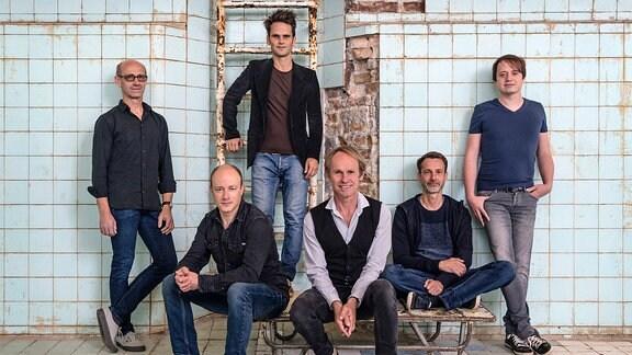Die Band Keimzeit, bestehend aus sechs männlichen Mitgliedern, posiert für die Kamera.