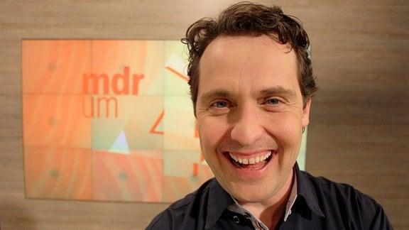 Stefan Ganß lacht im MDR um 4-Studio in die Kamera