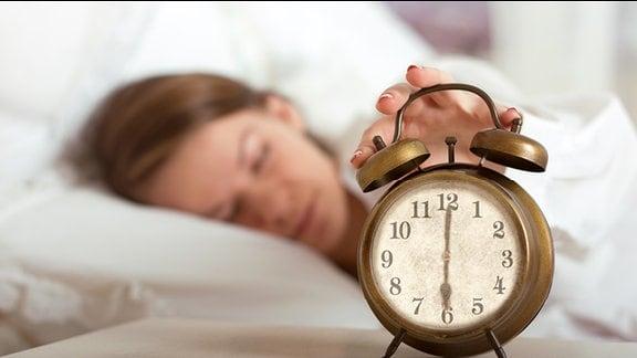 Eine Frau liegt im Bett und im Vordergrund ein Wecker.