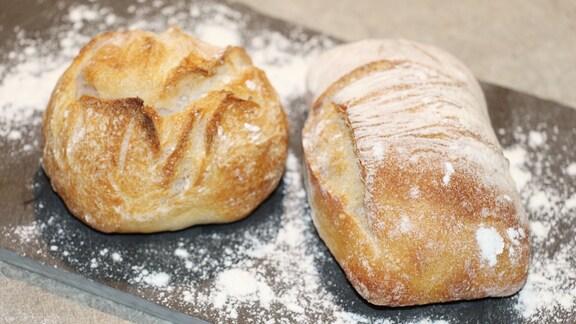 Frisch gebackene Brötchen liegen auf einem Brett.