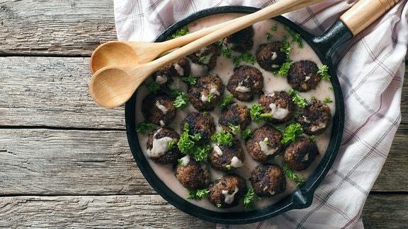 Köttbullar,  Schwedische Fleischbällchen in einer Pfanne mit heller Soße und Petersilie.