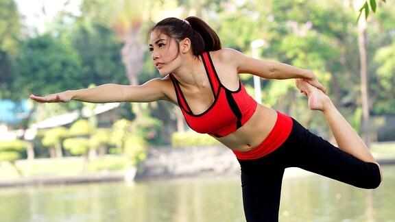 Eine Frau machtauf einer Wiese Sport