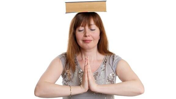 Eine Frau balanciert ein Buch auf ihrem Kopf