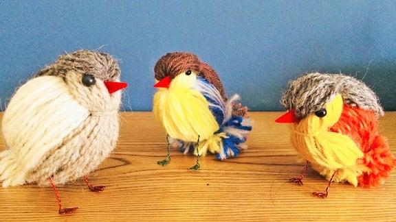 Vögel aus Wolle sitzen auf Holz