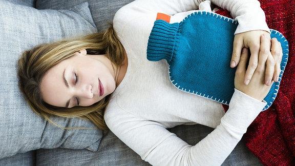 Frau mit Wärmflasche auf dem Bauch