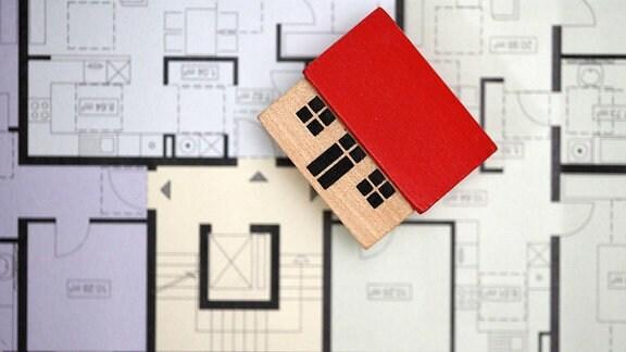 Ein Holzhäuschen liegt auf einem bunten Grundriss