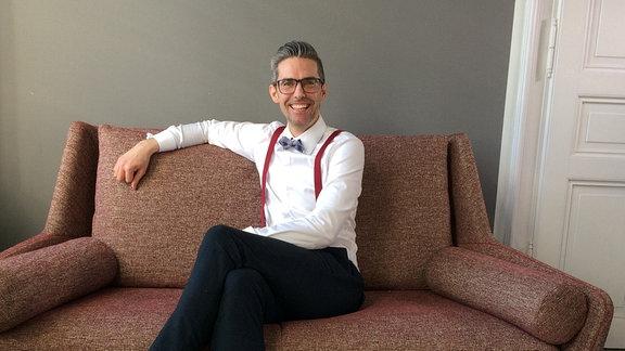 Einrichter Steffen Jacob Schmalz sitzt auf Sofa und lächelt in die Kamera