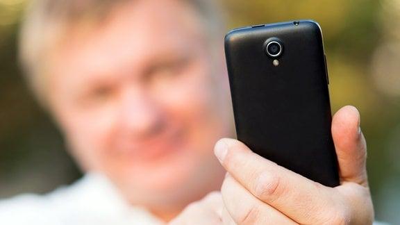 Ein Mann macht ein Selfie mit seinem Handy