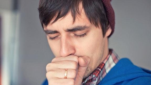 Ein junger Mann hält sich beim husten eine Hand vor den Mund