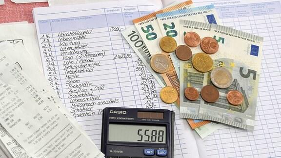 Haushaltsbuch liegt neben Geld und Taschenrechner auf dem Tisch.