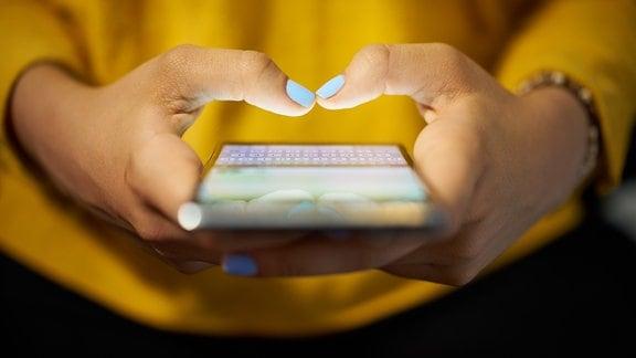 Die SMS wird am 3. Dezember 2017 25 Jahre alt. Mit dem Smartphone tippt eine Frau in einer gelben Bluse eine Textnachricht.