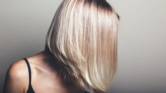 Frau, deren Gesicht von blonen Haaren verdeckt ist