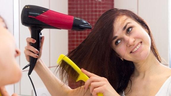 Eine junge Frau fönt sich die Haare