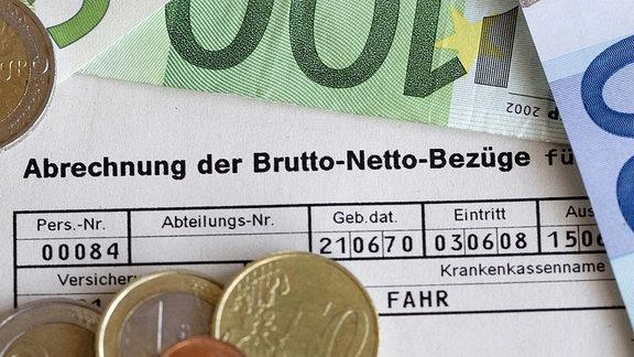 Lohn- und Gehaltsabrechnung, Verdienstbescheinigung - Euromünzen und -scheine liegen auf einer Lohnabrechnung.