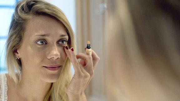 Junge Frau schminkt sich vor einem Spiegel.