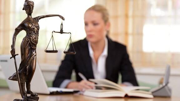 Vor einer Notarin steht eine Justitia auf einem Schreibtisch