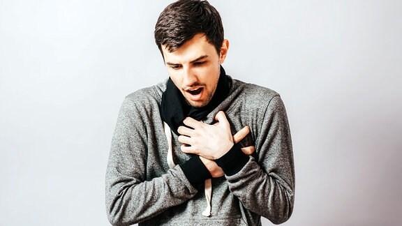 Themenbild Sodbrennen - Ein Mann greift sich röchelnd an die Brust.