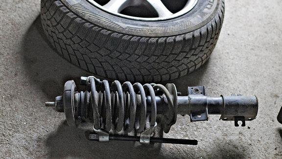 In einer Autowerkstatt liegen Rad und Stoßdämpfer ausgebaut auf dem Boden.