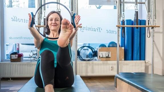 Sylvia Seifert liegt bei einer Beine-Po-Übung im Fitnessstudio auf einem Sportgerät.