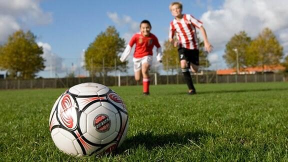 Zwei Jungs rennen auf einem Fußball zu.