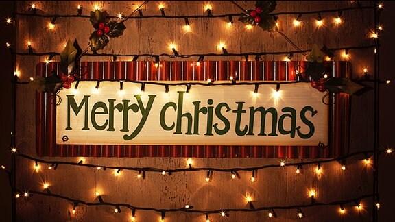 """""""Merry Christmas"""" steht auf einem von einer Lichterkette umgebenen Schild"""