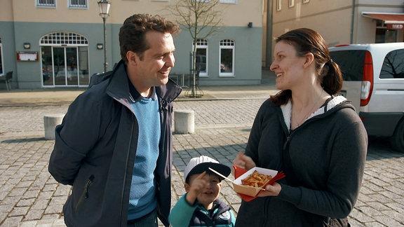 Reporter Stefan Ganß im Gespräch mit einer Frau, die eine Portion Pommes hält.