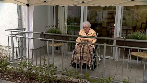Eine Seniorin sitzt in einem Rollstuhl auf einem Balkon.