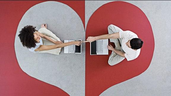 Symbolbild: Auf einem Teppich, der ein Herz zeigt, sitzen sich eine Frau und ein Mann mit Laptop gegenüber, deren Zeigefinger sich berühren