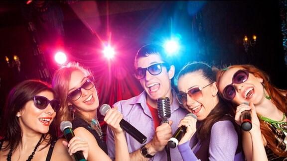 Vier Frauen und ein Mann mit Mikrophon in der Hand singen
