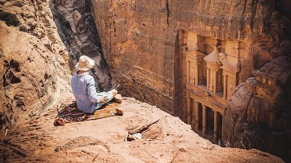 Tourist mit Sonnenhut sitzt auf Felsen und blickt von oben in die Schlucht Siq.