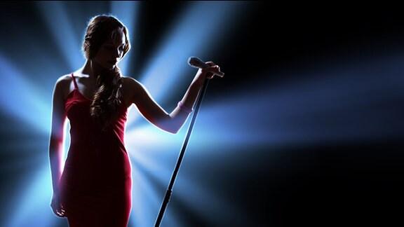 Eine Frau am Mikrofohn auf einer Bühne.