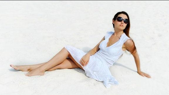 Posierendes Model mit blauem Sommerkleid und Sonnenbrille.