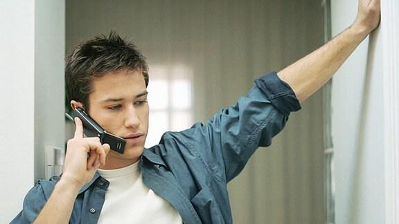 Ein junger Mann telefoniert mit einem Mobiltelefon