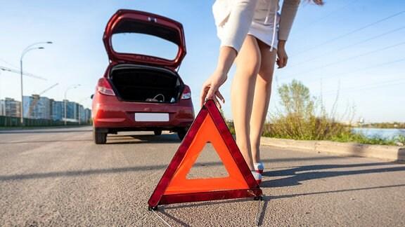 Symbolbild: Unfallort - Eine Frau stellt hinter ihrem Wagen ein Warndreieck auf.