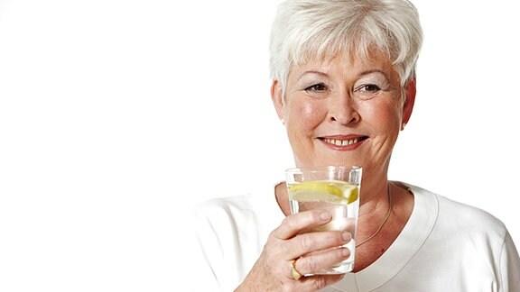 Eine grauhaarige Frau hat ein Glas Wasser mit Zitrone in der Hand