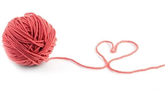 Rotes Wollknäuel, der abgerollte Faden bildet ein Herz
