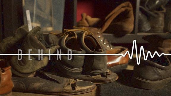 """Ein Stapel mit alten Schuhen sowie der Schriftzug """"Behind"""""""