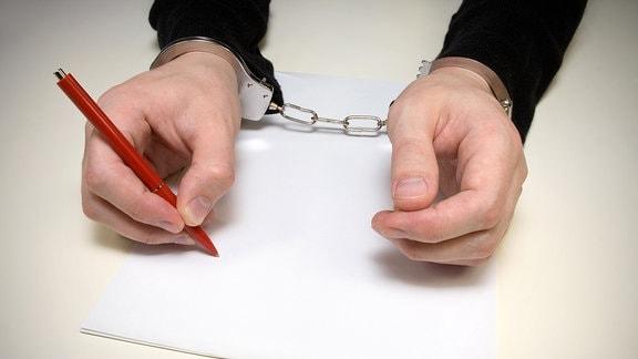 Hände in Handschellen halten einen Stift