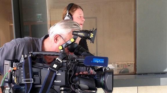 Mann steht an einer Kamera