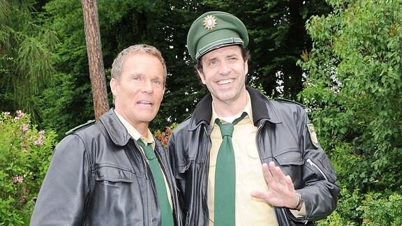 """Die Schauspieler Christian Tramitz (Hubert) und Helmfried von Lüttichau (r) lächeln während einer Drehpause zur Vorabendserie """"Hubert und Staller"""" in Münsing am Starnberger See (Oberbayern)."""