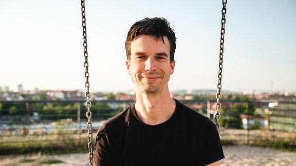 Portraitfoto von Prof. Martin Geisler auf Schaukel