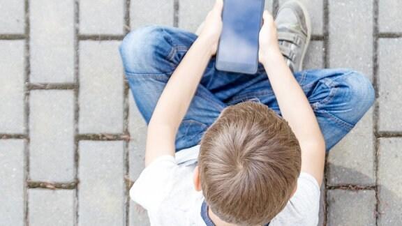 Ein Junge mit Handy.