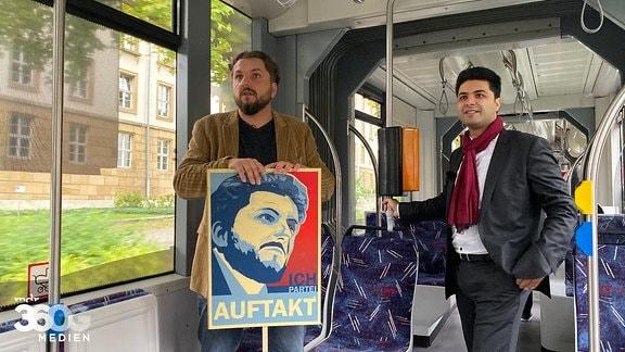 Dr. Reza Kazemi und Markus Hoffmann mit einem Wahlplakat in einer Straßenbahn in Erfurt.