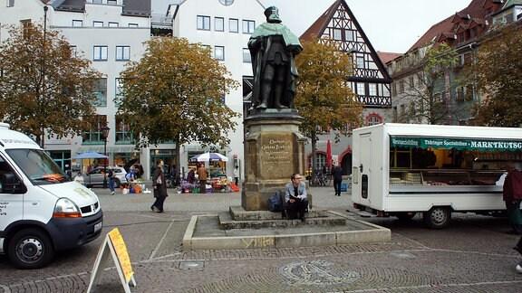 ein einsamer Mann auf dem Markt vor einem Denkmal sitzend, gerahmt von zwei Verkaufsständen