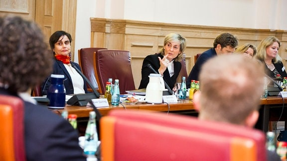 Männer und Frauen sitzen in einer Gesprächsrunde