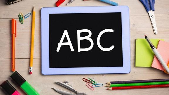 Tablet mit den Buchstaben ABC. Drum herum liegen Stifte.