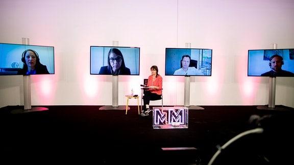Personen auf Bildschirmen zu sehen. Davor eine Frau auf einem Stuhl sitzend.